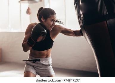 Vrouwelijke bokser die een enorme bokszak raakt in een boksstudio. Vrouw bokser hard trainen.