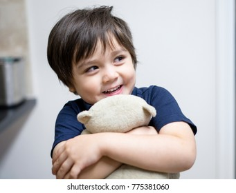 Happy kid boy hugging teddy bear with smiling face, Active little boy cuddle soft toy with big smile, Happy or healthy child concept