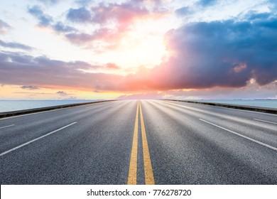 空のアスファルト高速道路と日没時の青い海の自然の風景