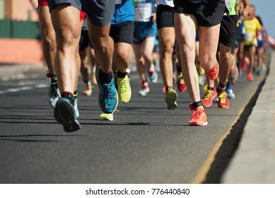 夕方の光の中で走るマラソン、足の都市道路の詳細を走る