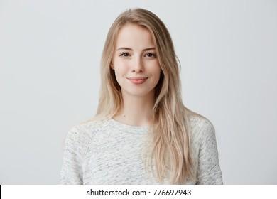Vrij glimlachend vreugdevol vrouw met blond haar, terloops gekleed, tevreden kijkend naar camera, gelukkig. Studio shot van knappe mooie vrouw geïsoleerd tegen lege studio muur.