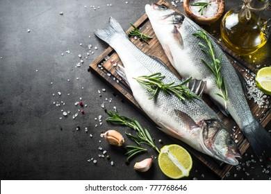 Frischer Fisch Seebarsch und Zutaten zum Kochen. Roher Fisch Seebarsch mit Gewürzen und Kräutern auf schwarzem Schiefertisch. Draufsicht mit Kopierraum.