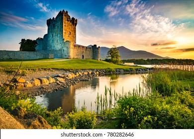 黄金の時間の間に誰もいない古代の要塞ロス城、アイルランドの湖、緑の草、オレンジ色の雲の遺跡