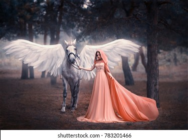 Beautiful, young elf, walking with a unicorn. She is dressed in a long orange dress with a cape, a hood. Artistic Photography