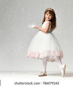 Modelo de niña pequeña en el vestido de invierno de comunión blanco se encuentra en corona de oro con gemas caras bajo nieve intensa en estudio sobre fondo gris