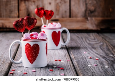 Hot chocolate with pink marshmallows in mugs with hearts on a wooden background for Valentine's day