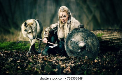 Warrior Woman  with a woolf in the woods. Viking girl. Reconstruction of a medieval scene