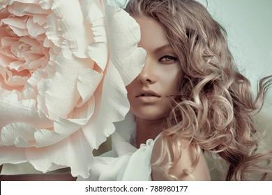 Schönes Porträt einer Frau mit großen Papierblumen