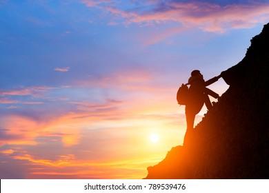 man climbing mountain at sunrise,conceptual scene