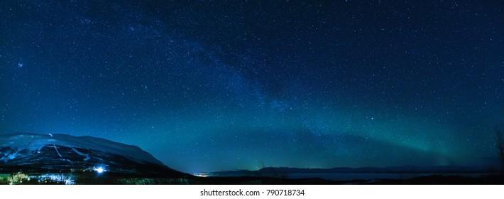 Winter panorama with Milky way and Northen lights phenomenon starting Aurora Borealis in Lapland scandinavia.
