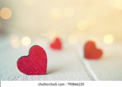 焦点がぼけたライトに対して木製のテーブルの上の赤いハートのクローズアップ。聖バレンタインデーの背景