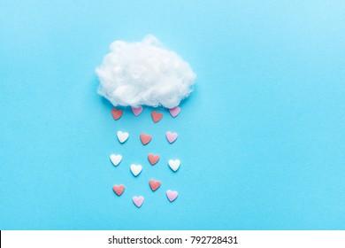 Bola de algodón Nube Lluvia Sugar Candy Sprinkle Hearts Rojo Rosa Blanco sobre fondo de cielo azul. Apliques Composición Artística Estilo Infantil. Concepto de caridad de amor de San Valentín. Tarjeta de felicitación con copia espacio