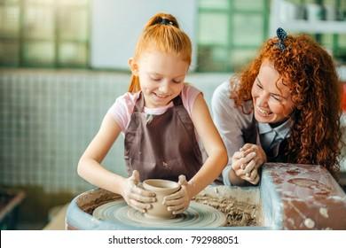 Junge rothaarige Mutter und ihre Kindertochter, die zusammen aus Ton auf Töpferscheibe formen