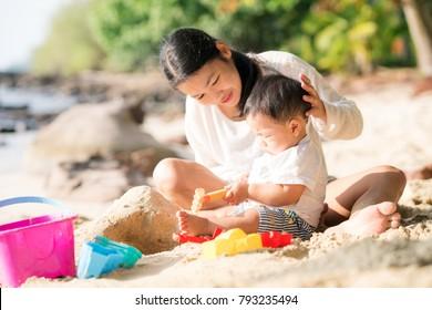 La madre y el bebé asiáticos juegan arena y juguetes togather en la playa
