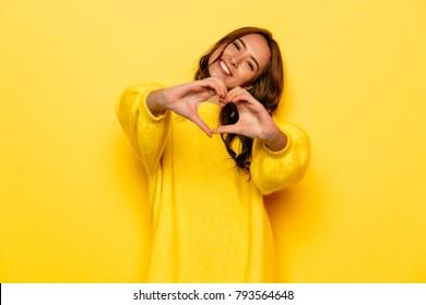 Lächelndes junges Mädchen im gelben Pullover, der Herz mit zwei Händen zeigt, Liebeszeichen. Isoliert über gelbem Hintergrund.