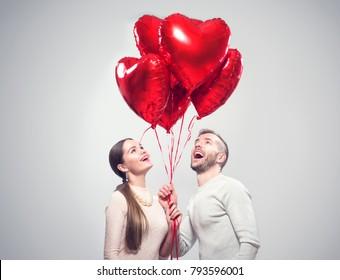 バレンタインカップル。笑顔の美しさの少女と彼女のハンサムなボーイフレンドの肖像画は、ハート形の気球の束を押しながら笑っています。幸せなうれしそうな家族。愛。幸せなバレンタインデー