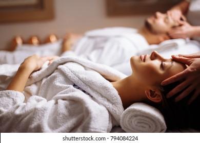 Pareja joven recibiendo masaje de cabeza en el spa de belleza
