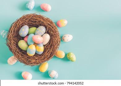 Кольорові великодні яйця в гнізді на фоні пастельних кольорів з простором.