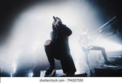 close-up silhouet van rap & trap & hiphop ster / zanger presteren op het podium van nachtclub. Donkere achtergrond, rook, concertschijnwerpers