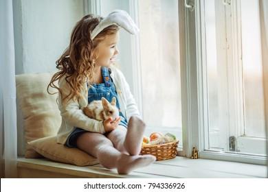 かわいい幸せな子供女の子は彼女の友人の小さなカラフルなウサギを保持している窓枠に座っているイースターの日にウサギの耳を着ています。
