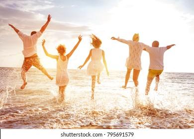 5人の幸せな人々のグループが走り、夕日に逆らって海のビーチにジャンプします