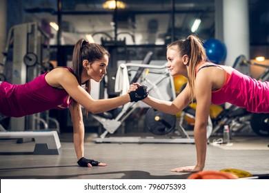 現代のジムでお互いを見ながら腕立て伏せをし、手をつないでいる2人の若いやる気のある攻撃的で魅力的な焦点を絞ったスポーティなアクティブな女の子。
