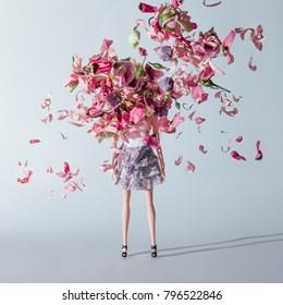 Muñeca niña con flores rosas y violetas. Concepto de moda minimalista creativo.
