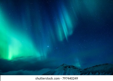 Erstaunlicher Blick auf das Nordlicht über hohe Berge, die mit Schnee, Naturgewalten, Aurora Borealis, Island bedecken