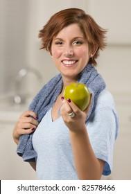 彼女のキッチンで緑のリンゴを保持しているタオルでかなり赤い髪の女性。