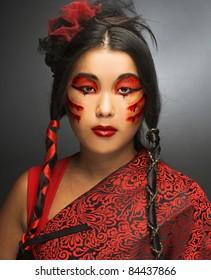 創造的なメイクアップと黒と赤のシルクの若い女性の肖像画