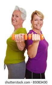 ダンベルでフィットネストレーニングをする幸せな年配の女性