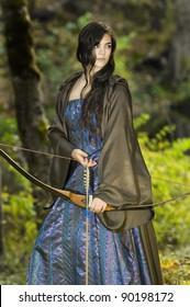 ウッドランズの弓を持つ美しい若い女性レンジャー