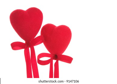 Two red Valentine's Hearts with ribbons tied below. The image is isolated on a white background