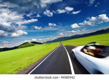 Berglandschaft mit Straße und fahrendem Auto