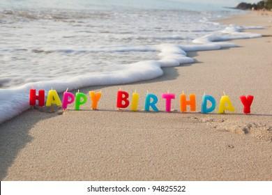 Velas de feliz cumpleaños en una playa.