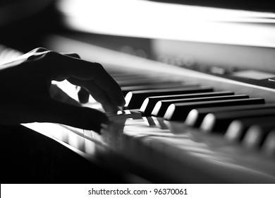 電子ピアノで演奏する手。閉じる。被写界深度が浅い。黒と白。