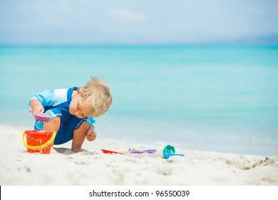 Cute Baby Boy jugando con juguetes de playa en playa tropical