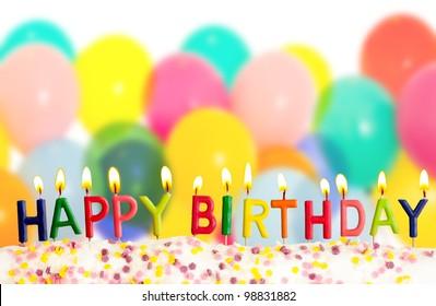 Feliz cumpleaños velas encendidas sobre fondo de globos de colores