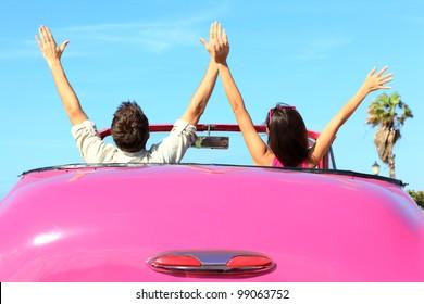 Vrijheid - gelukkig gratis paar in auto rijden in roze vintage retro auto juichen vrolijk met opgeheven armen. Vrienden gaan op road trip reizen op zomerdag onder zon blauwe hemel.