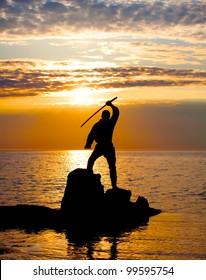 Mann mit Schwert nahe dem Meer zur Sonnenuntergangszeit