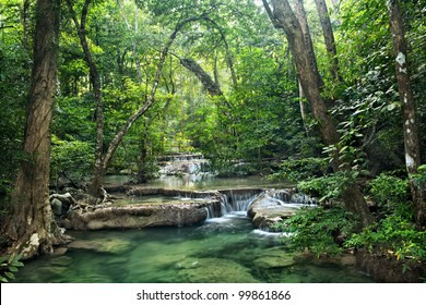 Background of streaming waterfall. Erawan waterfall is famous in Thailand. Around of brook has green jungle from big tree.The forest protected by forester all time. It is a beautiful landscape