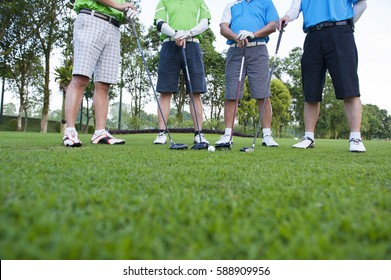 Image of 4 male golfers with drivers and a white golf ball standing on the fairway