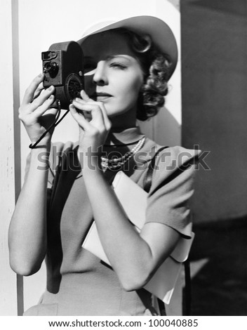 Portrait of a young woman taking a picture with a camera
