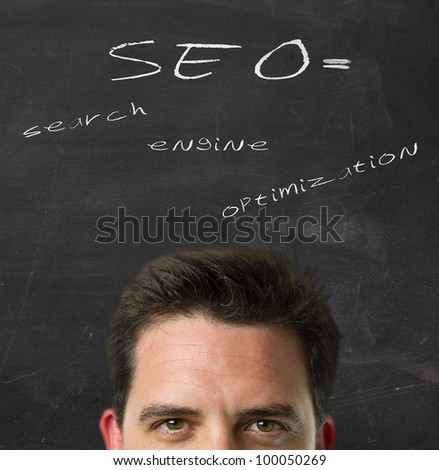 Business man over blackboard with the explanation of the acronym SEO