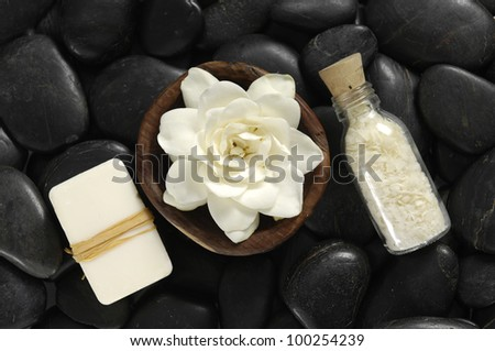 gardenia flower ib wooden bowl with salt in glass on black pebbles #100254239