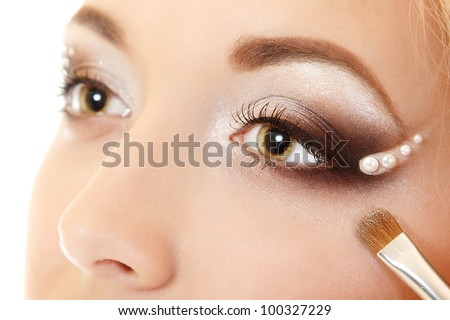 beauty makeup portrait of young beautiful woman with hand of esthetician applying eyes shadow with brush isolated on white background #100327229