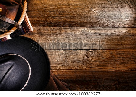 American West rodeo cowboy black felt hat with tools of the trade and authentic brown leather western boots with spur on old weathered ranch barn wood floor as a grunge background