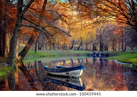 Colorful autumn landscape.Nature background.Boat on the lake in the autumnal forest #100419445