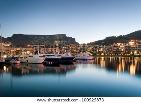 Victoria and Alfred Waterfront as the hot summers sun sets behind Table Mountain and the night lights start to shine Royalty-Free Stock Photo #100525873