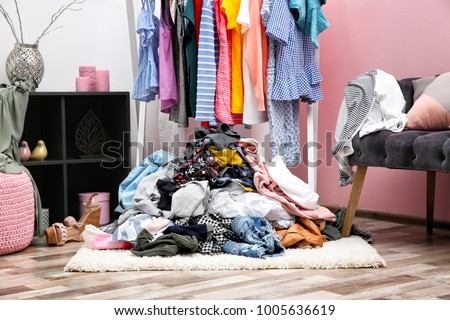 Messy dressing room interior with clothes rack Royalty-Free Stock Photo #1005636619